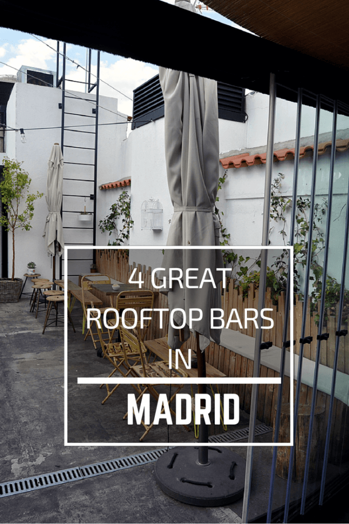 """view of a rooftop bar in Madrid, there is a grey folded parasol in the foreground, a metal ladder going up to the roof, wooden chairs and tables and plants growing on the railings. Text overlay in white reads """"4 Great Rooftop Bars in Madrid, Spain"""""""