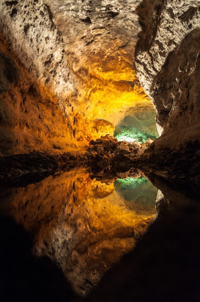 Inside of a lava tunnel with green adn golden light and water reflections
