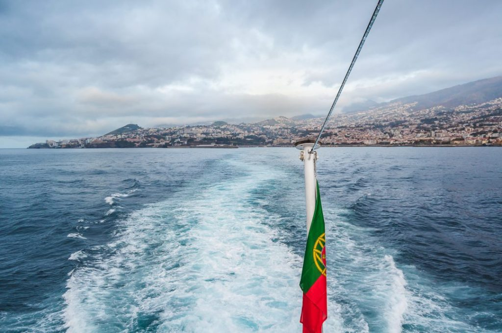 View of a harbour from the back of a ferry early in the morning on a cloudy day, in the foreground is a portuguese flag twisted in its pole.