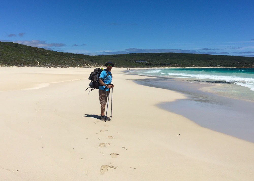 Man smiling on hiking gear in the middle of a gold sand beach on a sunny day