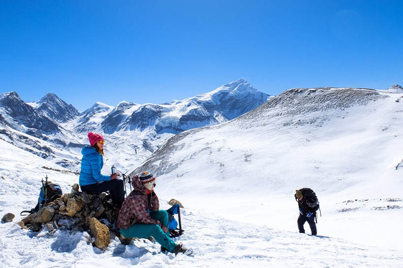 Group of people sitting on a mountain covered in snow on a bright sunny day