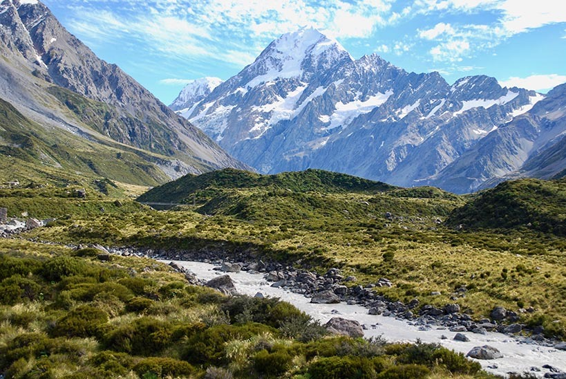 Views of a river flowing through a valley with a snow-capped mountain in the background on a sunny day
