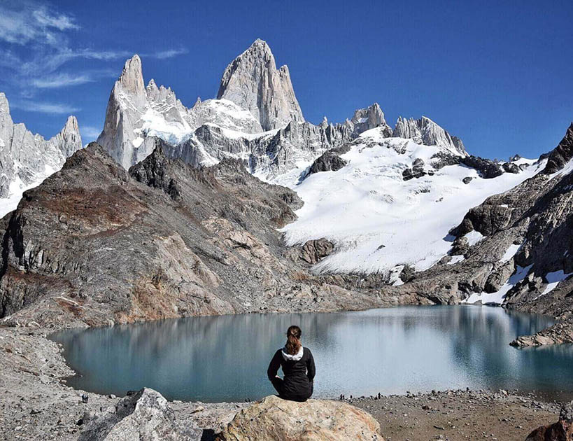 Brunette girl sitting by a lake with her back to the camera looking at Mount Fitz Roy in the Patagonia on a cloudless day