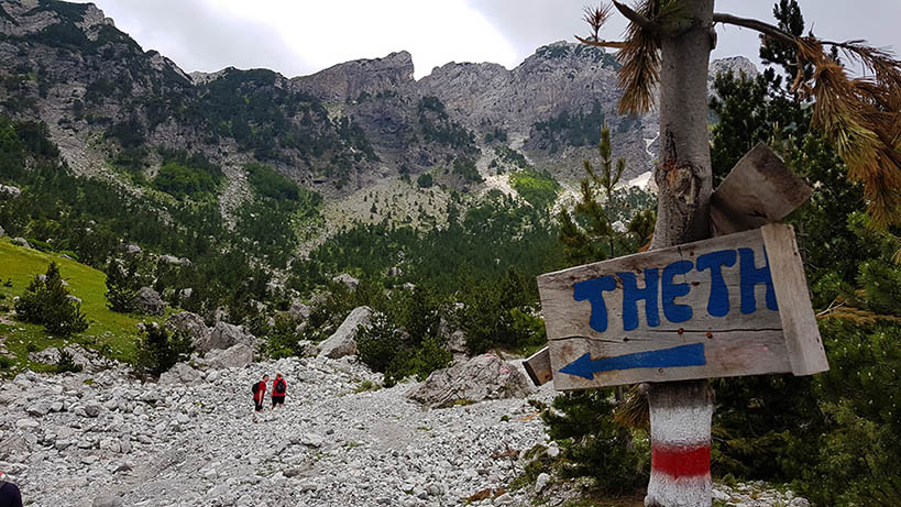 Wooden sign on a path in the Albanian Alps pointing left with Thethi painted on it with blue paint.