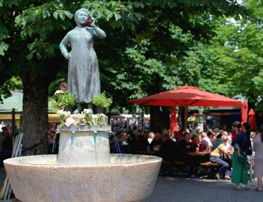 An image of a beer garden in Munich. At the forefron there is a fountain with a statue of a women holding a flower to her ear, a big red parasol is in the background. Lots of people are sitting under the parasol enjoying their drinks.