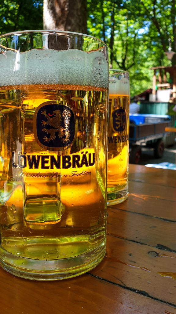 2 glasses of Lowenbräu Radler and Helles on a wooden table at a Beer Garden in Bavaria