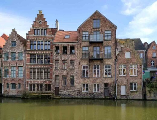view of the facade of various brick buildings by a canal